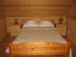 Двуспальная кровать и прикроватная тумбочка.